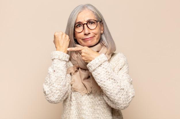 Niecierpliwa i wściekła kobieta w średnim wieku, wskazująca na zegarek, prosząca o punktualność, chce być punktualna