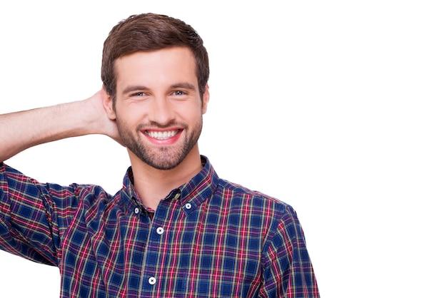 Niedbale przystojny. portret przystojnego młodego mężczyzny w casualowej koszuli trzymającej rękę za głową i uśmiechającego się stojąc na białym tle