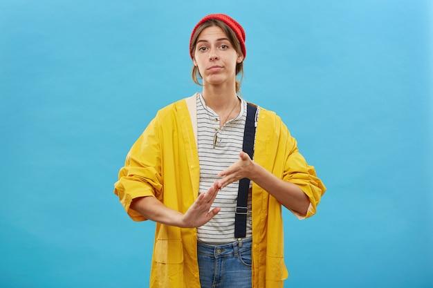 Niedbale ubrana pracownica zaciera ręce po zakończeniu pracy na białym tle na niebieskiej ścianie.
