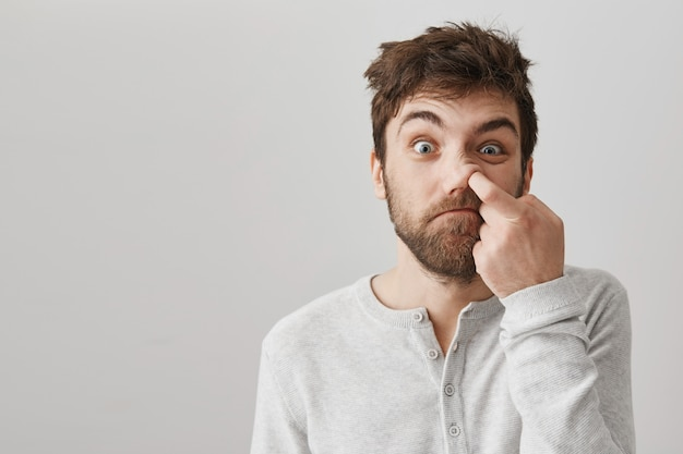 Niedbały brodaty facet z potarganymi włosami dłubiącymi w nosie