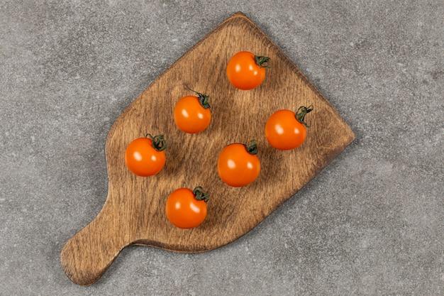 Niedojrzały pomidor na desce do krojenia, na marmurze.