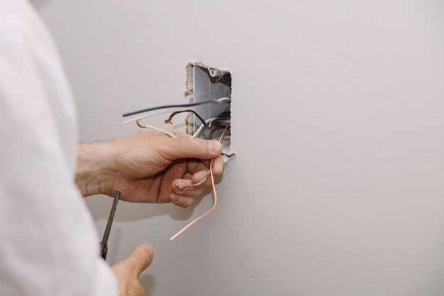 Niedokończone gniazdo elektryczne z przewodami elektrycznymi i złączem zainstalowanym w płycie gipsowo-kartonowej