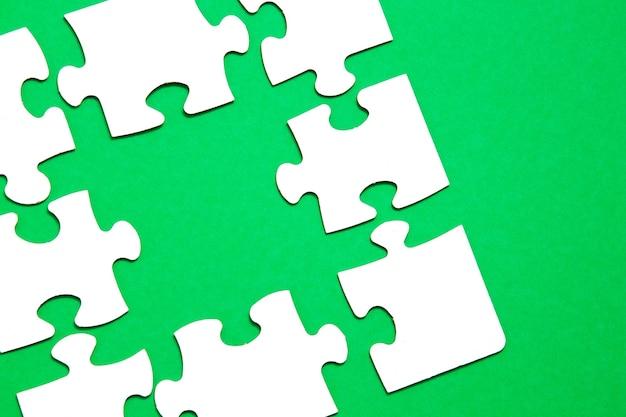 Niedokończone puzzle na zielonym tle, koncepcja budowania zespołu