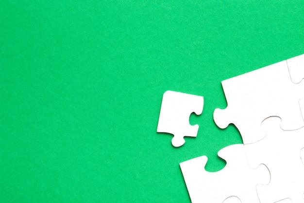 Niedokończone puzzle wykonane z białego kartonu na białym tle