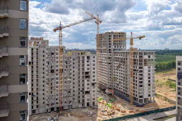 Niedokończone wielokondygnacyjne domy i trzy dźwigi budowlane na nowej konstrukcji