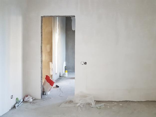 Niedokończony budynek. surowe wykończenie mieszkania. pomieszczenie z otynkowanymi ścianami betonowymi. remont wnętrz.