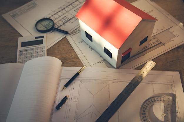 Niedokończony dom i dokumenty na tle tabeli