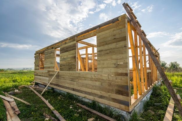 Niedokończony ekologiczny dom w budowie w zieleni polu na niebieskim niebie. rowy wypełnione cementowymi i drewnianymi ścianami z otworami okiennymi przyszłego wygodnego domku w cichej okolicy.