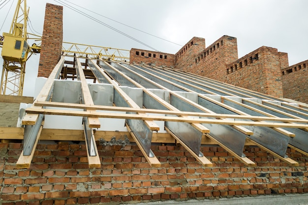 Niedokończony murowany budynek mieszkalny z drewnianą konstrukcją dachu w budowie.