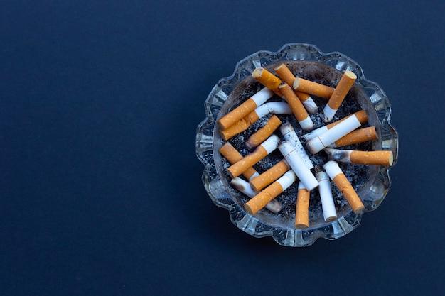 Niedopałki papierosów w szklanej popielniczce na ciemnym tle.