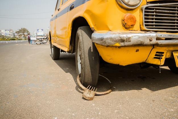 Niedorzeczna domowa ochrona przed kradzieżą żółtych taksówek w indiach. humorystyczna, przezabawna, komiczna koncepcja bezpieczeństwa i ochrony przed kradzieżą auta. przebita opona. przebicie opony samochodowej. ukłucie