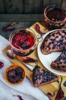 Niedoskonałe ciasto jagodowe. przytulne domowe przyjęcie na herbatę. drewniany stół i biała pościel.