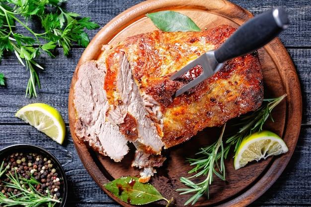 Niedzielna pieczona polędwica wieprzowa, soczysty i soczysty kawałek mięsa z pieca nacierany musztardą i przyprawami: rozmarynem, liściem laurowym, sokiem z limonki i pieprzem na drewnianym tle, zbliżenie, widok z góry