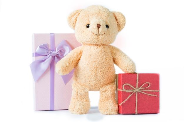 Niedźwiadkowa lala z czerwonym i purpurowym prezenta pudełkiem na białym tle odizolowywającym.