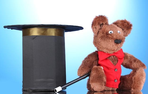 Niedźwiedź i czarny cylinder na niebieskim tle