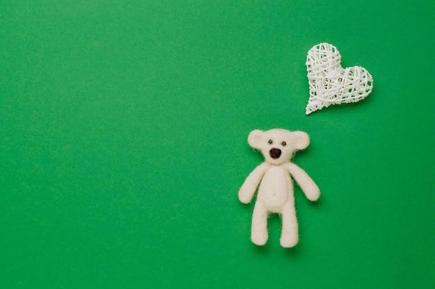 Niedźwiedź zabawka i naturalne serce dla dziecka na zielonym tle z pustym miejscem na tekst. widok z góry, płaski układ.