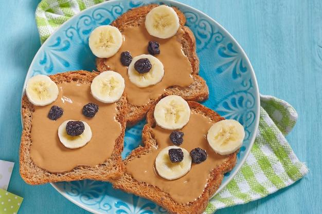 Niedźwiedzie z pieczywa pełnoziarnistego z masłem orzechowym, bananem i rodzynkami