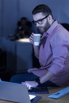 Nieformalna atmosfera. przystojny, inteligentny, przyjemny it mężczyzna siedzi na stole i naciska przycisk na laptopie podczas picia kawy