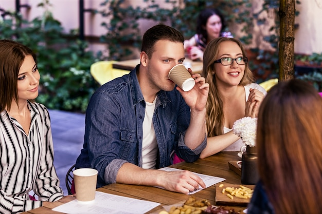 Nieformalna przyjazna impreza z kolegami z pracy w przytulnej kawiarni z pysznymi przekąskami w ciepły letni dzień