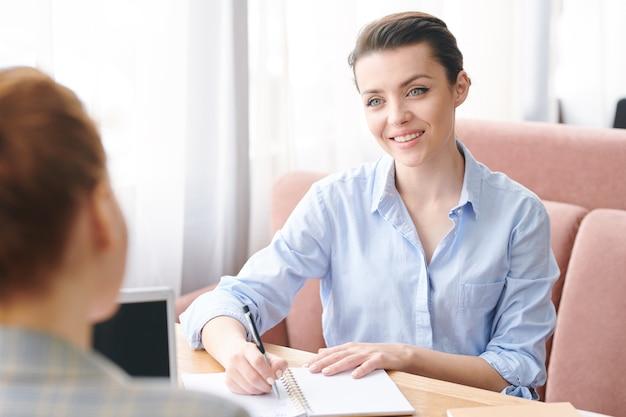 Nieformalna rozmowa kwalifikacyjna w kawiarni: uśmiechnięta przyjazna rekrutacja w niebieskiej bluzce siedzi przy stole i robi notatki w organizatorze, rozmawiając z kandydatem o wcześniejszym doświadczeniu
