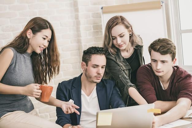 Nieformalny zespół projektantów biurowych omawiający pracę grupową