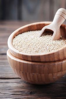Niegotowana komosa ryżowa na drewnianym stole