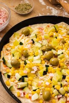 Niegotowana pizza pod dużym kątem ze składnikami na patelni