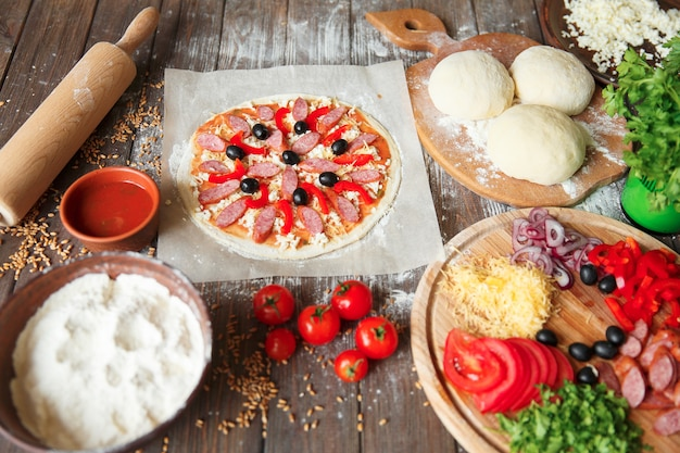 Niegotowana pizza ze składnikami na stole