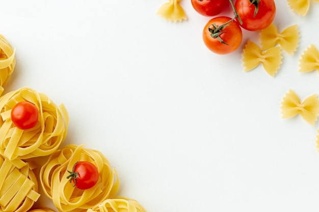 Niegotowane farfalle tagliatelle i pomidory z miejsca na kopię