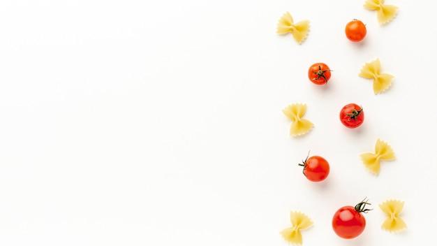 Niegotowane farfalle ustawienie z pomidorami z miejsca na kopię