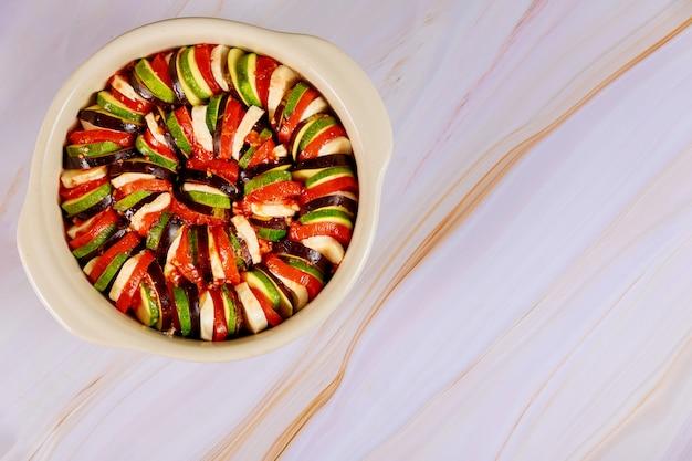 Niegotowane francuski wegetariańskie jedzenie ratatouille na białym tle.