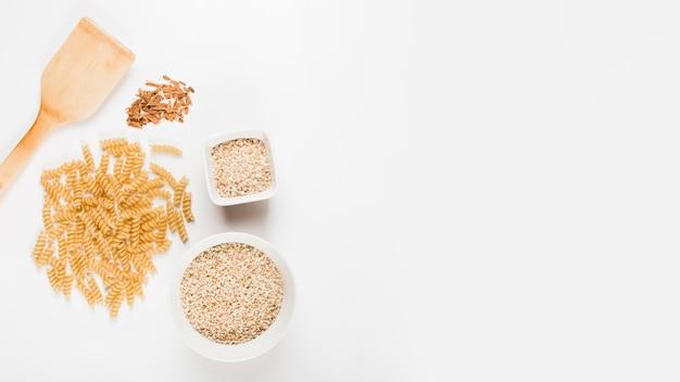 Niegotowane fusilli makaron; ryż i zgnieciony cynamon z łopatką na białym tle