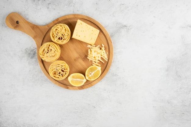 Niegotowane gniazda spaghetti, drewniana deska z serem cytrynowym.