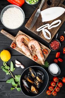 Niegotowane hiszpańskie składniki paelli z krewetkami królewskimi, mątwą, małżami i ziołami na czarnym drewnianym stole, widok z góry, zdjęcie jedzenia.