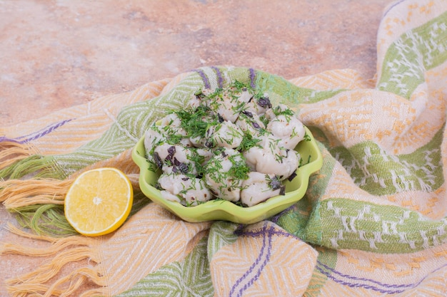 Niegotowane kaukaskie chinkali z posiekanymi ziołami w misce.