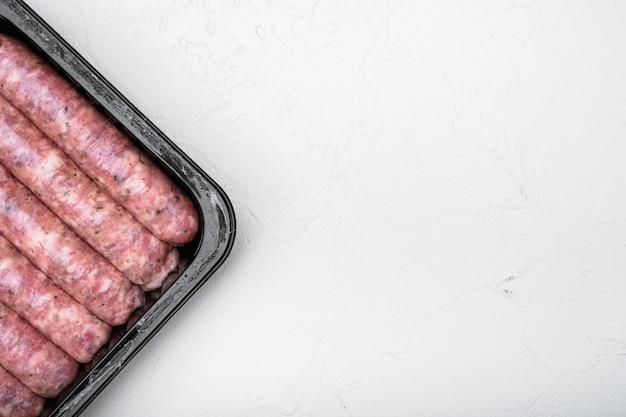 Niegotowane kiełbaski mięsne w zestawie z tworzywa sztucznego, na białym tle kamiennego stołu, widok z góry na płasko, z miejscem na kopię na tekst