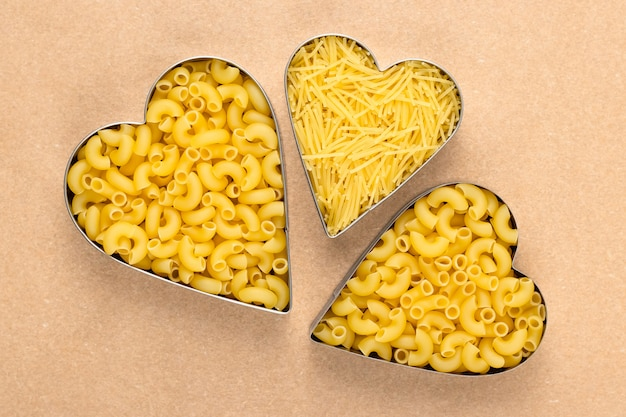 Niegotowane makarony na brązowym papierze. surowy makaron w kształcie serca. kupa żółtych makaronów.