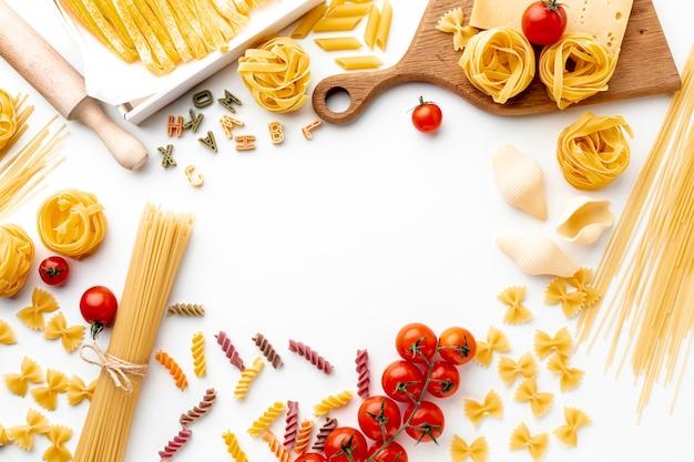 Niegotowane makarony ułożone płasko z pomidorami i twardym serem