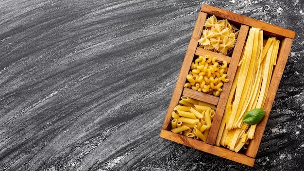 Niegotowane makarony w drewnianym pudełku z miejsca kopiowania