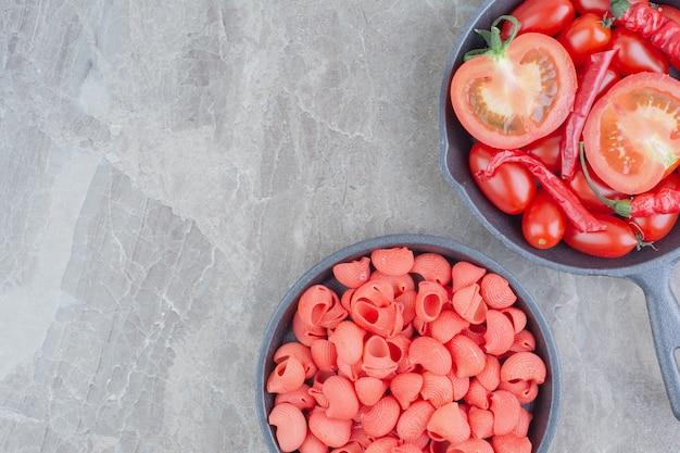 Niegotowane makarony z pomidorkami koktajlowymi i chilli na czarnej patelni