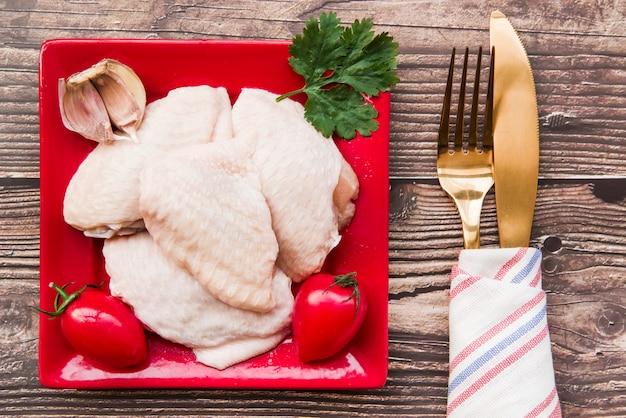 Niegotowane mięso i składniki w płytkę ze złotym widelcem i nożem masła