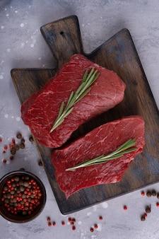 Niegotowane mięso wołowe z przyprawami i rozmarynem na desce do krojenia
