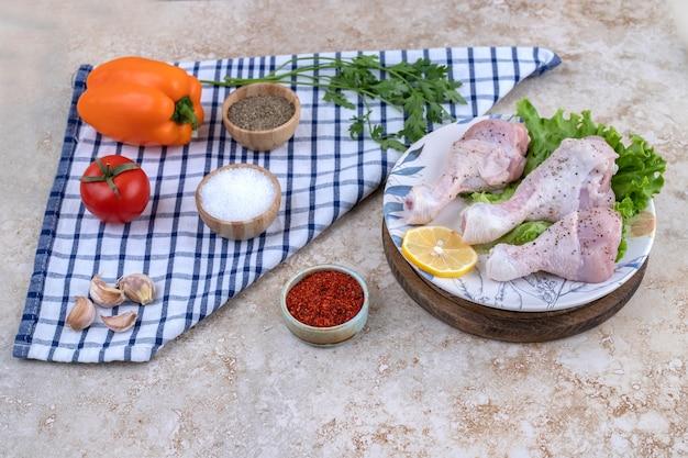 Niegotowane mięso z udek kurczaka z warzywami na drewnianej desce