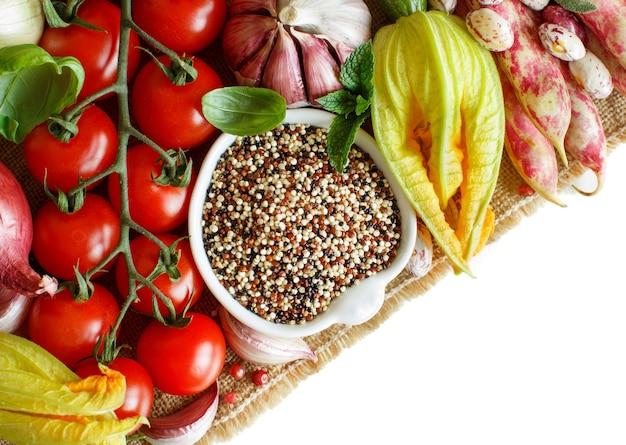 Niegotowane mieszane quinoa z warzywami na białym tle