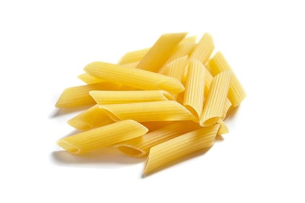 Niegotowane penne rigate włoski makaron, na białym tle
