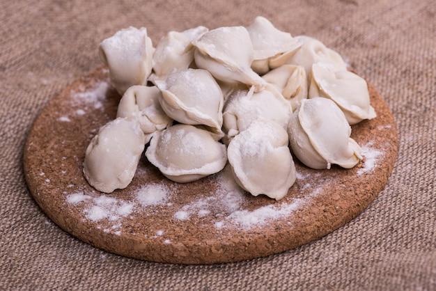 Niegotowane pierogi pelmeni. tradycyjne danie rosyjskie. tło z pelmeni ułożone na desce do krojenia