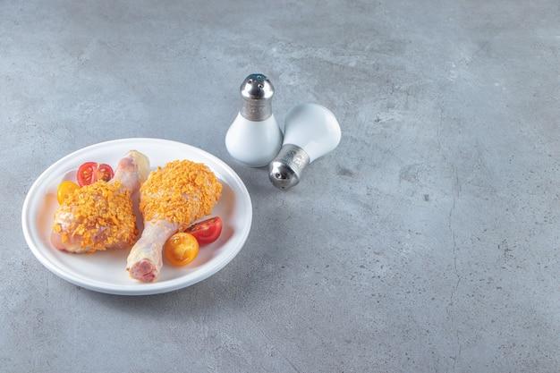 Niegotowane podudzia na talerzu obok soli, na marmurowym tle.