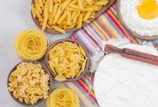 Niegotowane różne rodzaje makaronów z mąką i surowym jajkiem na obrusie.
