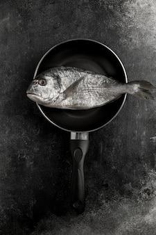 Niegotowane ryby z owoców morza na patelni