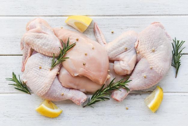 Niegotowane skrzydełka i udka z kurczaka, marynowane w składnikach do gotowania - świeży surowy kurczak z rozmarynowymi ziołami cytrynowymi i przyprawami